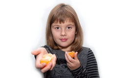 Предназначенная для подростков девушка делит мандарин Стоковые Фотографии RF