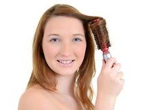 Предназначенная для подростков девушка завивая ее волос Стоковое фото RF