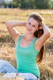 Предназначенная для подростков девушка отдыхая в поле Стоковое Изображение