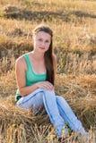 Предназначенная для подростков девушка отдыхая в поле Стоковое Изображение RF