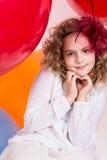 Предназначенная для подростков девушка показывает руку на шариках предпосылки сердца больших резиновых Стоковая Фотография RF