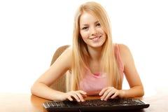 Предназначенная для подростков девушка при клавиатура смотря камеру с интересом любит внутри стоковая фотография