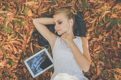 Предназначенная для подростков девушка при цифровая таблетка лежа на листьях Стоковое Изображение RF