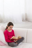 Предназначенная для подростков девушка сидя на кресле дома и читая a Стоковые Изображения