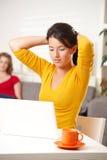 Предназначенная для подростков девушка смотря компьтер-книжку Стоковая Фотография