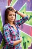 предназначенная для подростков девушка стоя близко стена надписи на стенах. Стоковая Фотография