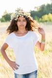 Предназначенная для подростков девушка с венком маргариток в поле Стоковые Изображения RF