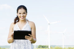 Предназначенная для подростков девушка с компьютером таблетки рядом с ветротурбиной. стоковая фотография