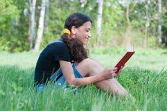 Предназначенная для подростков книга чтения девушки на природе Стоковые Фотографии RF