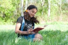 Предназначенная для подростков книга чтения девушки на природе Стоковое Изображение RF