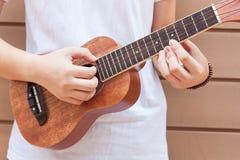 Предназначенные для подростков азиатские женщины с гавайской гитарой в ее свободном времени Стоковые Фотографии RF