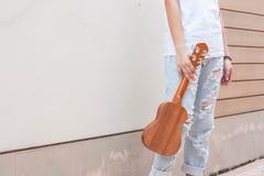 Предназначенные для подростков азиатские женщины с гавайской гитарой в ее свободном времени Стоковое Фото