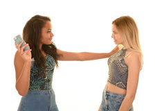 Предназначенные для подростков девушки воюя над телефоном Стоковое фото RF