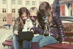 Предназначенные для подростков девушки используя компьтер-книжку на стенде в улице города Стоковое Фото