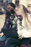 Предназначенные для подростков девушки используя компьтер-книжку на стенде Стоковые Фотографии RF