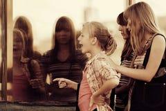 Предназначенные для подростков девушки смотря через окно мола Стоковое фото RF