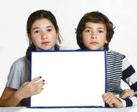 Предназначенные для подростков дети мальчик и девушка держат лист чистого листа бумаги Стоковые Изображения RF