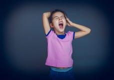 Предназначенные для подростков зевки девушки хотят спать на сером цвете Стоковые Фотографии RF