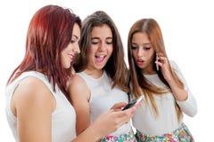 Предназначенные для подростков подруги играя на умных телефонах Стоковое фото RF