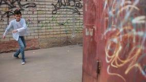 Предназначенные для подростков танцы мальчика, танцы улицы на предпосылке кирпичной стены сток-видео