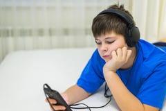 Предназначенный для подростков используя сотовый телефон с наушниками Стоковое Изображение RF
