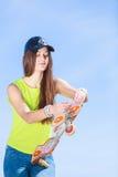 Предназначенный для подростков конькобежец девушки с скейтбордом на улице Стоковые Фотографии RF