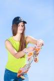 Предназначенный для подростков конькобежец девушки с скейтбордом на улице Стоковая Фотография RF