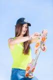Предназначенный для подростков конькобежец девушки с скейтбордом на улице Стоковое Фото