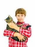 Предназначенный для подростков мальчик держит его кота tabby в его оружиях стоковые фото