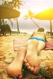 Предназначенный для подростков мальчик положенный на ноги пляжа вне стоковое фото