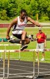 Предназначенный для подростков мальчик скачет барьер - легкая атлетика - NY стоковое изображение