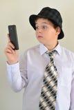 Предназначенный для подростков мальчик с сюрпризом смотрит мобильный телефон Стоковые Изображения RF