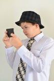 Предназначенный для подростков мальчик с сюрпризом смотрит мобильный телефон Стоковые Фотографии RF