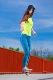 Предназначенный для подростков скейтборд катания конькобежца девушки на улице Стоковая Фотография RF