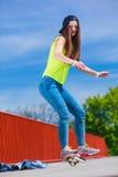 Предназначенный для подростков скейтборд катания конькобежца девушки на улице Стоковое Фото