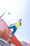 Предназначенный для подростков скейтборд катания конькобежца девушки на улице Стоковая Фотография
