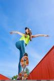 Предназначенный для подростков скейтборд катания конькобежца девушки на улице Стоковые Изображения RF