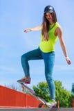Предназначенный для подростков скейтборд катания конькобежца девушки на улице Стоковое Изображение RF