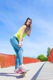 Предназначенный для подростков скейтборд катания конькобежца девушки на улице Стоковые Фото