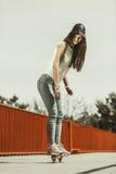 Предназначенный для подростков скейтборд катания конькобежца девушки на улице Стоковое Изображение