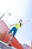Предназначенный для подростков скейтборд катания конькобежца девушки на улице Стоковое фото RF