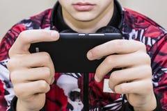Предназначенный для подростков смотря мобильный телефон Стоковая Фотография