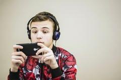 Предназначенный для подростков смотря мобильный телефон Стоковое Изображение