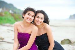 2 предназначенных для подростков девушки в элегантных платьях усмехаясь совместно на пляже Стоковые Изображения