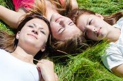 3 предназначенных для подростков девушки лежа на траве Стоковое Изображение RF