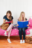 2 предназначенных для подростков девушки делая домашнюю работу совместно Стоковые Фотографии RF