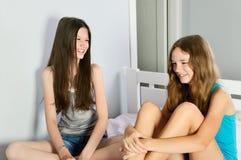 2 предназначенных для подростков девушки имея сидеть потехи смеясь над на кровати Стоковое Изображение