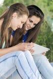 2 предназначенных для подростков девушки с вашим Таблетк-ПК в природе Стоковые Изображения RF