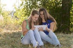 2 предназначенных для подростков девушки с вашим Таблетк-ПК в природе Стоковые Фотографии RF