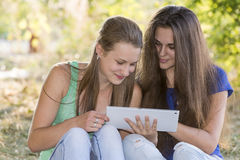 2 предназначенных для подростков девушки с вашим Таблетк-ПК в природе Стоковое фото RF